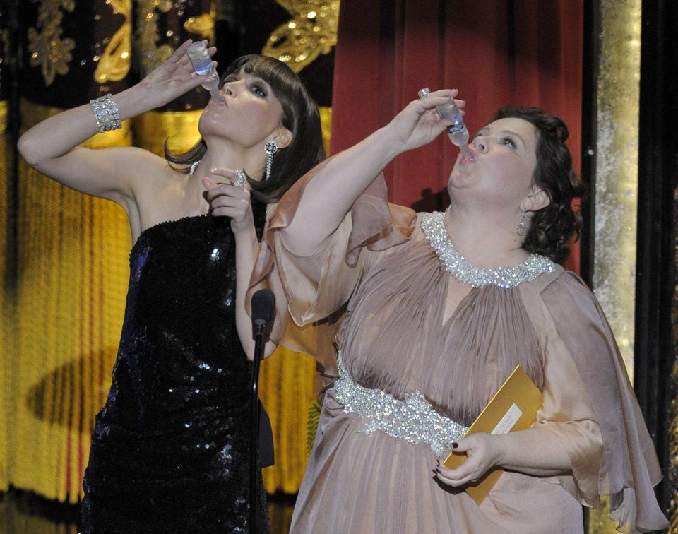Rose Byrne y Melissa McCarthy beben en el escenario de los Oscar 2012