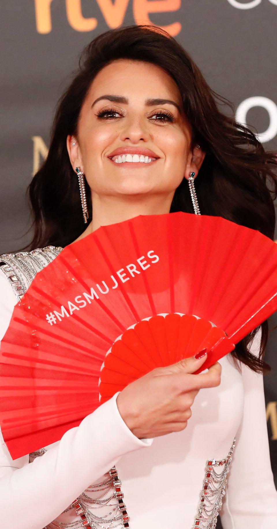 Penélope Cruz con un abanico rojo en apoyo a las mujeres en la alfombra roja de los Goya 2018