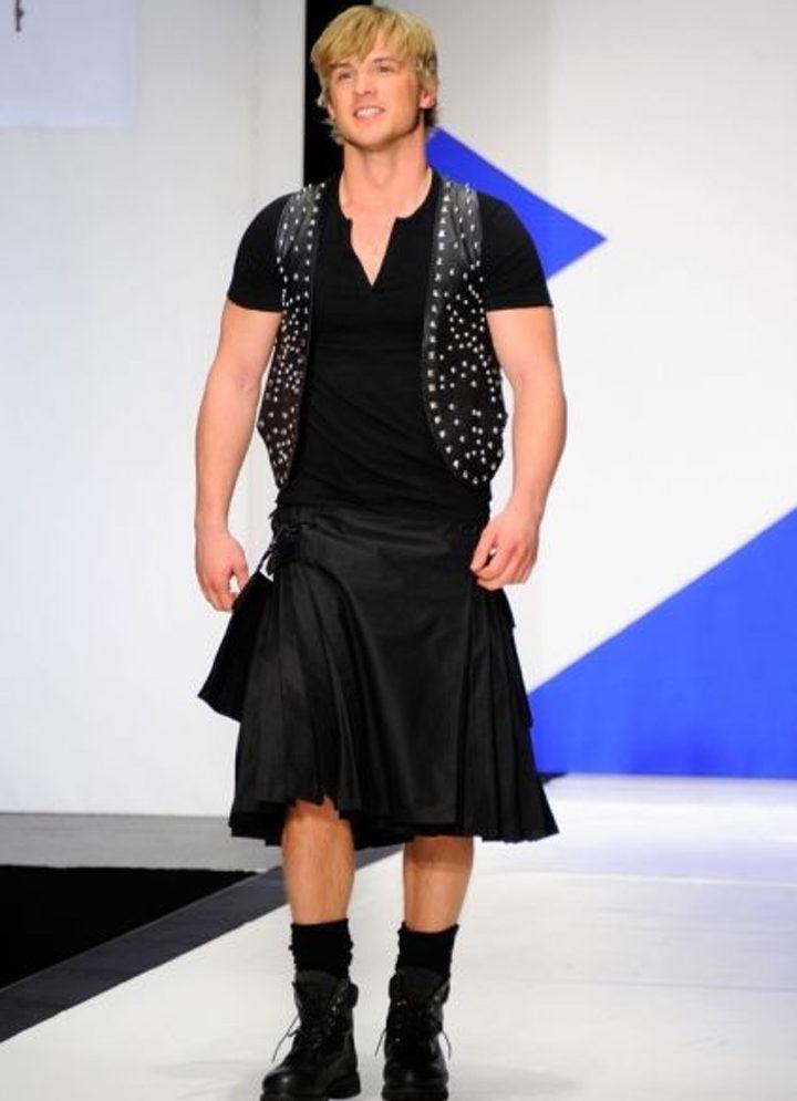 Freddie Stroma desfilando en una pasarela con falda y chaleco