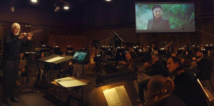 Foto del artículo de Vanity Fair con John Williams dirigiendo a su orquesta con una imagen de la Princesa Leia de fondo